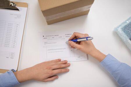 Photo pour close up of woman filling postal form at office - image libre de droit