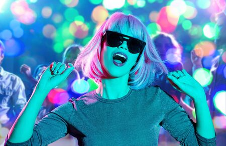 Photo pour nightlife, entertainment and people concept - happy young woman wearing pink wig and black sunglasses dancing at nightclub over lights background - image libre de droit
