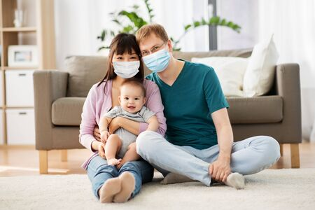 Photo pour family with baby in medical masks at home - image libre de droit