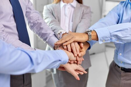 Photo pour gesture, people and teamwork concept - close up of business team stacking hands at office - image libre de droit