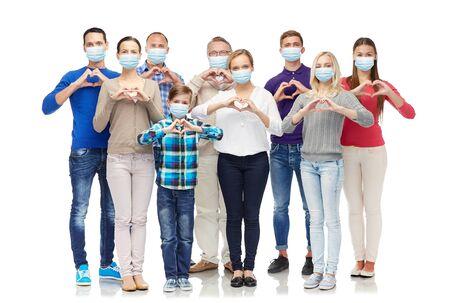 Photo pour people in medical masks making hand heart gesture - image libre de droit