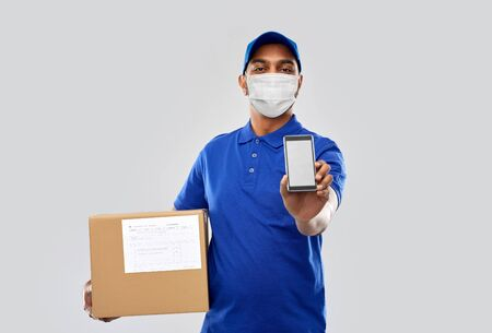 delivery man in mask with cellphone and parcel box