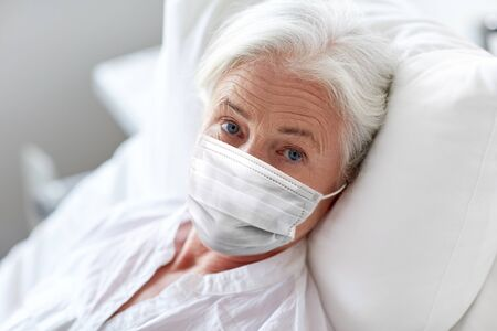 Photo pour old woman patient in mask lying in bed at hospital - image libre de droit