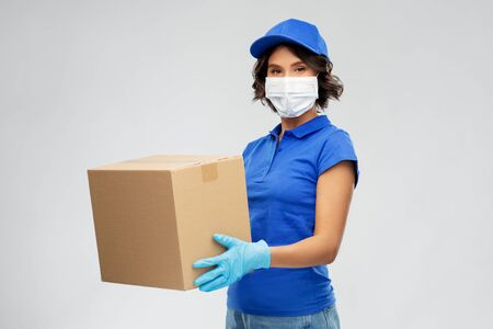 Photo for delivery woman in face mask holding parcel box - Royalty Free Image