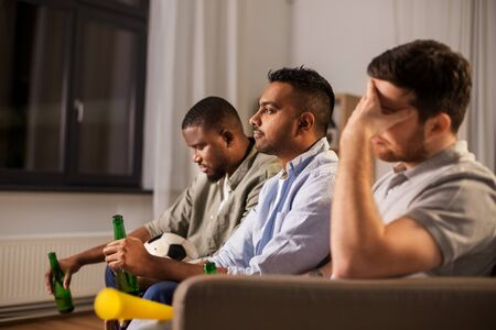 Photo pour sad friends with ball and vuvuzela watching soccer - image libre de droit