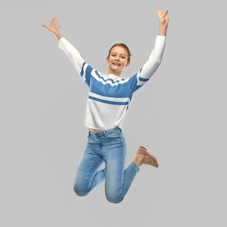 Photo for smiling teenage girl in pullover jumping - Royalty Free Image