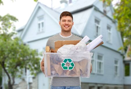 Photo pour smiling young man sorting paper waste over house - image libre de droit