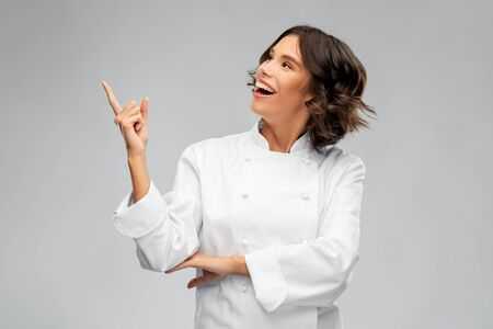 Photo for cooking, advertisement and food concept - happy smiling female chef in toque pointing finger up over grey background - Royalty Free Image