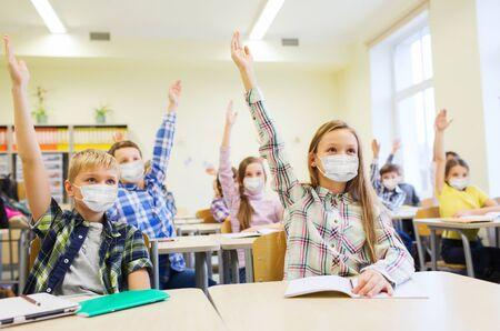 Photo pour group of students in masks raising hands at school - image libre de droit