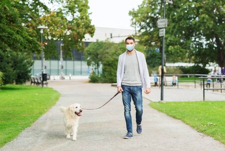 Photo for man in mask with labrador dog walking in city - Royalty Free Image