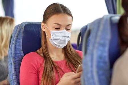 Photo pour woman in mask using smartphone in travel bus - image libre de droit
