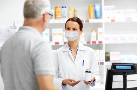 Photo pour apothecary in mask and senior customer at pharmacy - image libre de droit