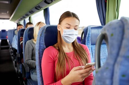 Photo for woman in mask with smartphone in travel bus - Royalty Free Image