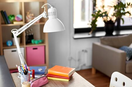 Photo for interior, home and education concept - room with lamp and school supplies on table - Royalty Free Image