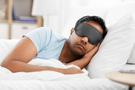 Photo pour indian man in eye mask sleeping in bed at home - image libre de droit