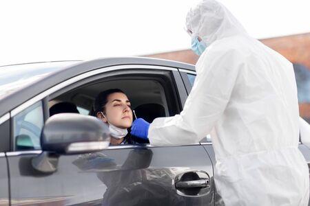 Photo pour healthcare worker making coronavirus test at car - image libre de droit
