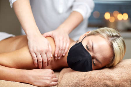 Foto de beauty and health safety concept - woman wearing face medical mask for protection from virus lying with closed eyes and having hand massage in spa - Imagen libre de derechos