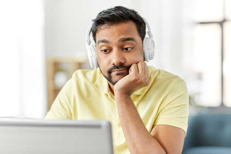Photo for bored man in headphones with laptop works at home - Royalty Free Image