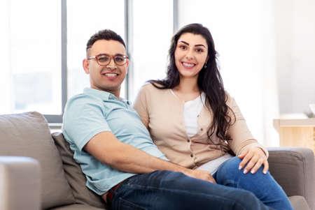 Photo pour happy couple sitting on sofa at home - image libre de droit