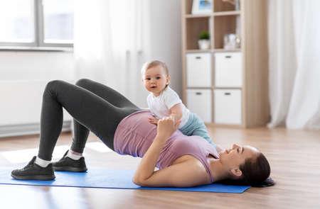 Foto de happy mother with little baby exercising at home - Imagen libre de derechos