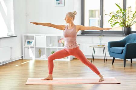 Photo pour woman doing yoga warrior pose at home - image libre de droit