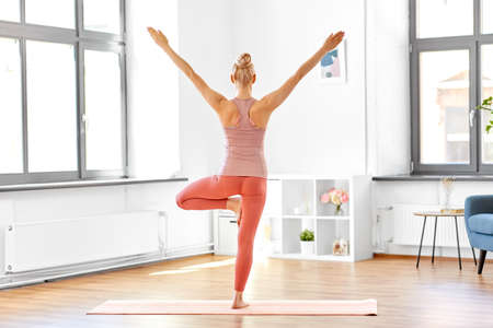 Photo for young woman doing yoga tree pose at home - Royalty Free Image