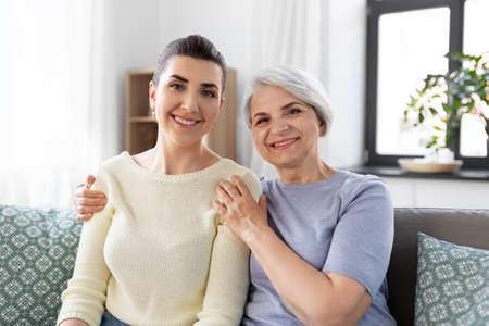 Photo pour senior mother with adult daughter hugging at home - image libre de droit