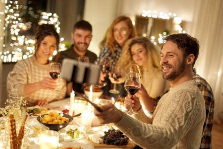 Photo pour friends taking selfie at christmas dinner party - image libre de droit