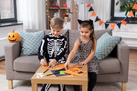 Photo for kids in halloween costumes doing crafts at home - Royalty Free Image