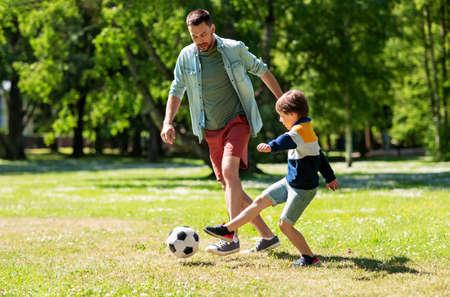 Photo pour father with little son playing soccer at park - image libre de droit