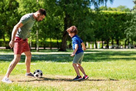 Foto de father with little son playing soccer at park - Imagen libre de derechos