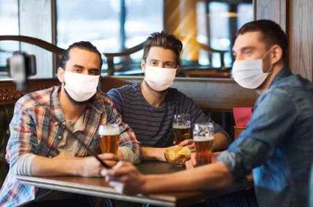 Photo for men in masks take selfie and drink beer at bar - Royalty Free Image
