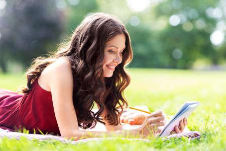 Photo pour happy woman with diary or notebook at park - image libre de droit
