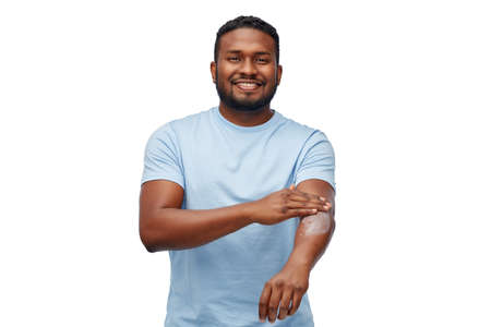 Foto de happy african man applying moisturizer to his hand - Imagen libre de derechos
