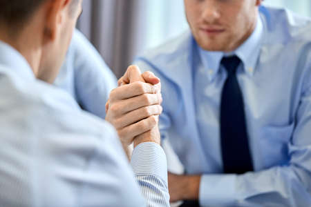 Photo pour close up of businesspeople arm wrestling at office - image libre de droit