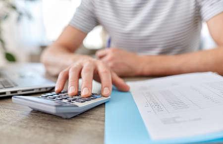 Foto de man with files and calculator works at home office - Imagen libre de derechos