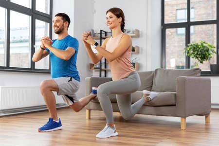 Photo pour happy couple exercising and doing squats at home - image libre de droit