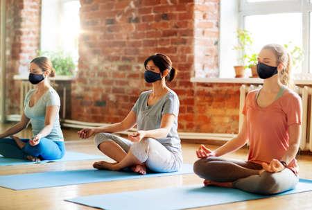 Photo pour group of women in masks doing yoga at studio - image libre de droit