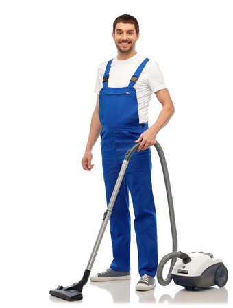 Photo pour male worker cleaning floor with vacuum cleaner - image libre de droit