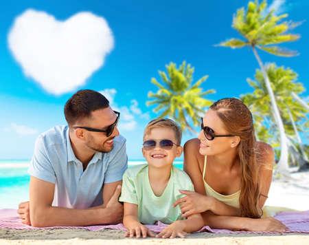 Photo pour happy family lying over tropical beach background - image libre de droit