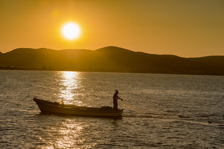 lonely fisherman at sunset