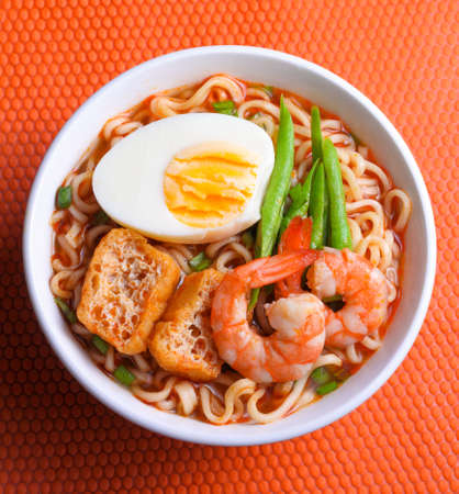 Hot and spicy instant noodle isolated on the orange color background