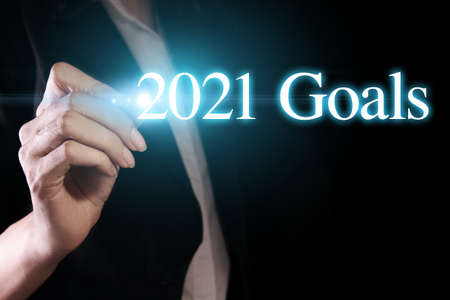 Photo pour Hand holding a pen and writing 2021 goals, wish you all the best as always in this coming new year. - image libre de droit