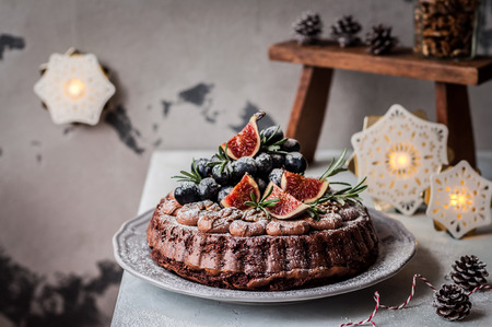 Photo pour Chocolate Christmas Cake Decorated with Figs, Grapes, Walnuts and Rosemary - image libre de droit
