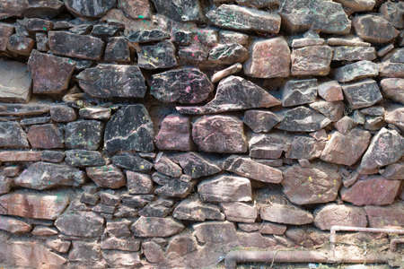 Photo pour Grunge background stone wall texture. Rough old stone or rock textured of mountains. Coarse facing, grungy aged stonework city. Front antique decor house. General layout of stone masonry. - image libre de droit