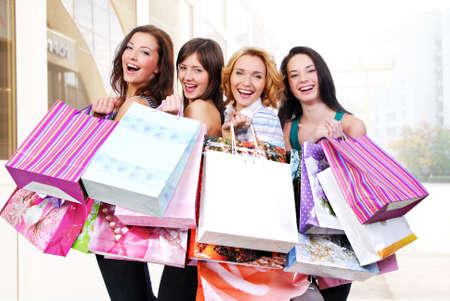 Foto de Group of happy smiling women shopping with colored bags  - Imagen libre de derechos