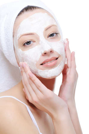 beautiful young woman doing cosmetic mask on her face - white background
