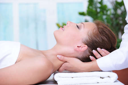 Neck massage for young woman relaxing in spa salon