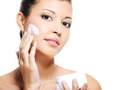 Beauty asian female skincare of her face by applying cosmetic cream on her cheek