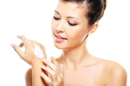 Beauty smiling female  applying cosmetic cream on her hands - over white backgroundの写真素材